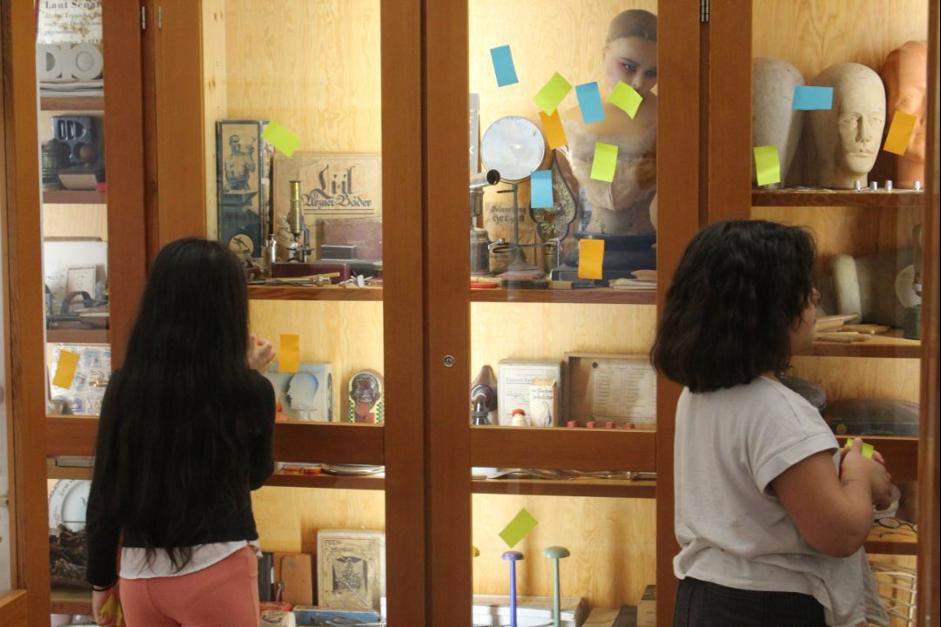 Veranstaltungsfoto, zwei Kinder vor einer Vitrine aus Holz und Glas, an dem verschiedenfarbige Post-Its kleben