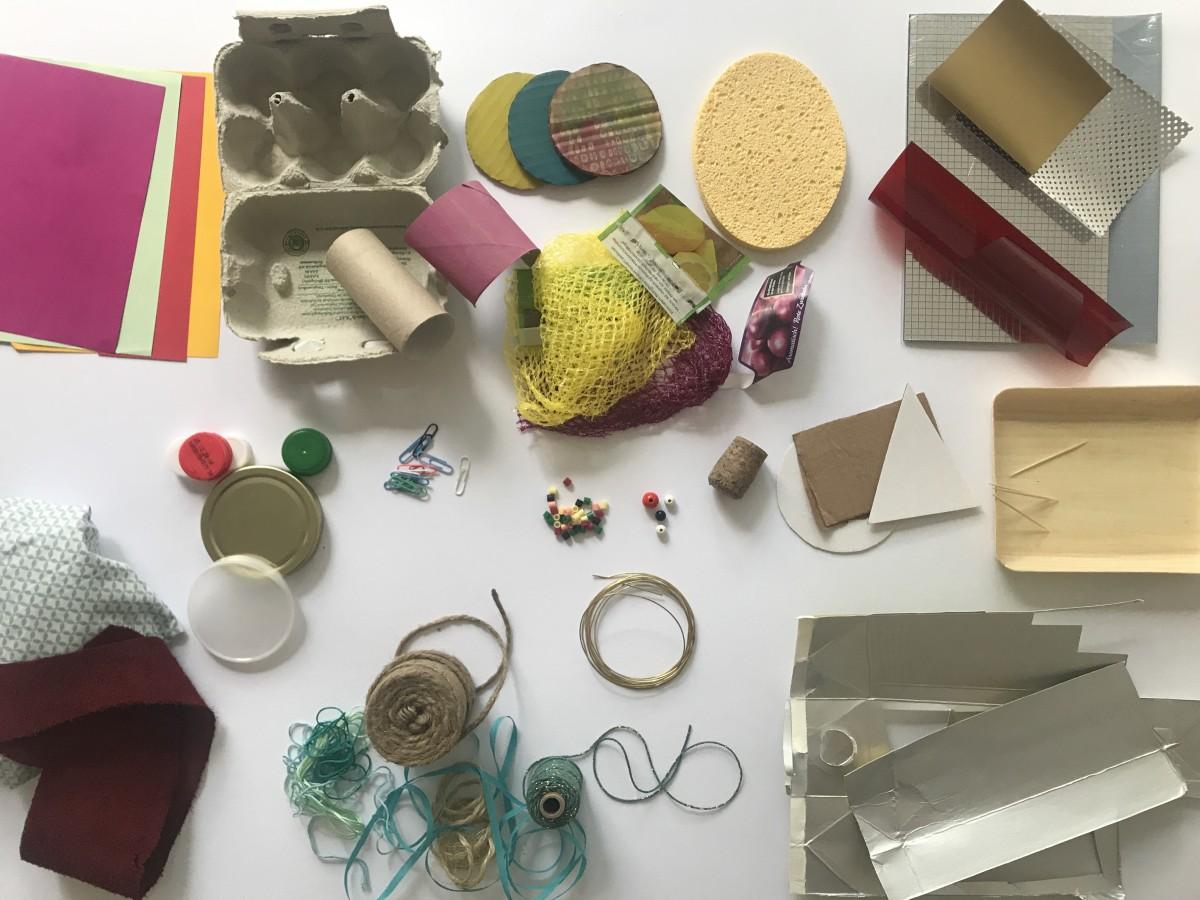 Aufsicht auf verschiedene Bastelmaterialien auf einer weißen Fläche, darunter Schnüre, Kartons, Kugeln und Lebensmittelnetze
