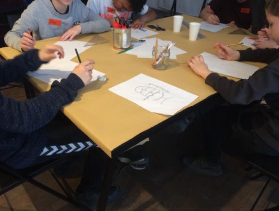 Kinder sitzen an einem Tisch und basteln, auf dem Tisch liegen Papiere und Gläser mit Bastelutensilien