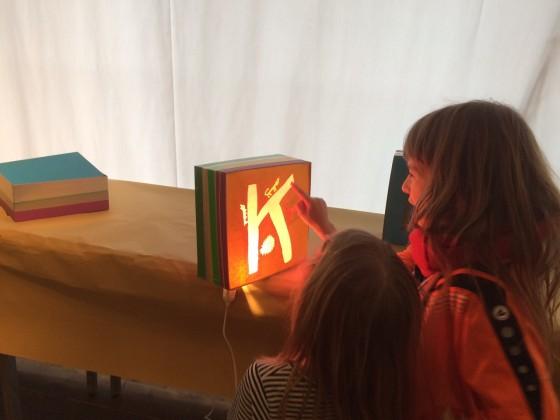 Zwei Kinder betrachten einen Lichtkasten mit einer Öffnung in Form eines K, durch das Licht hindurchscheint